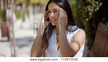 Young woman suffering from a headache pausing in an urban street to rub her temples with her fingers to relieve the pain