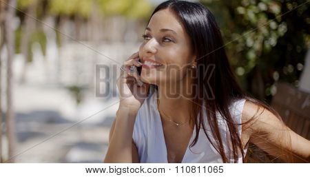 Vivacious gorgeous young woman chatting on her mobile phone with a smile of pleasure as she stands outdoors in an urban park