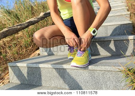 young fitness woman runner  tying shoelace on mountain stairs