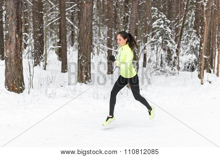 young fit athlete woman running at forest Sprinting during winter training outside in cold snow weat