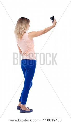 back view of standing young beautiful  woman  and using a mobile phone. girl  watching.  backside view of person.  Isolated over white background. Blonde in blue pants makes self on a compact camera.