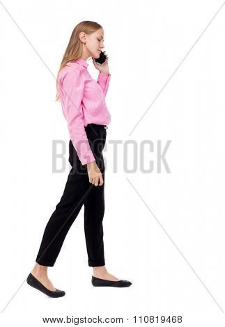 side view of a woman walking with a mobile phone. back view ofgirl in motion.   Rear view people collection. Isolated over white background. Woman office worker in a pink shirt is right on the phone.