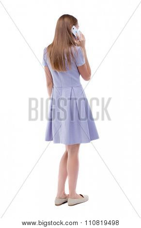 back view of a woman talking on the phone.  backside view of person.  Rear view people collection. Isolated over white background. The girl in a blue dress is white smartfonfon pressed to his ear.