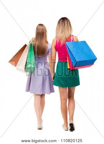 back view of  two walking women  with shopping bags. backside view of person.  Isolated over white background. Two pretty girls in fancy dresses go ahead with shopping bags thrown over his shoulders.