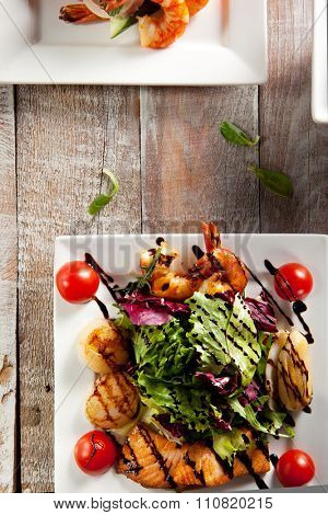 Seafood Salad - Shrimps, Sea Scallops, Squids and Salmon. Garnished with Fresh Raw Salad Leaf and Cherry Tomato