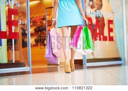 Female shopper with paperbags walking down mall