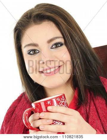 Closeup of a beautiful teen girl smiling at the viewer as she holds a red mug of hot cocoa.  She's wearing red fleece while wrapped in a red blanket. On a wite background.