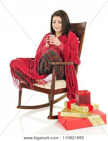 A beautiful teen girl waiting for her hot chocolate to cool as she's snuggled under a blanket in her pajamas.  A small stack of gifts are nearby.  On a white background.