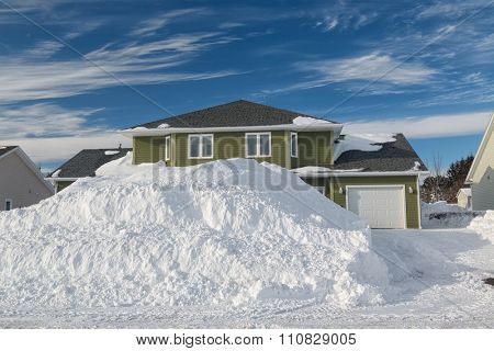 Giant snowbanks along a freshly plowed road in a north American neighborhood.