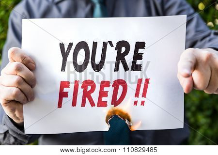 Businessman Is Holding A Burning Paper With Text