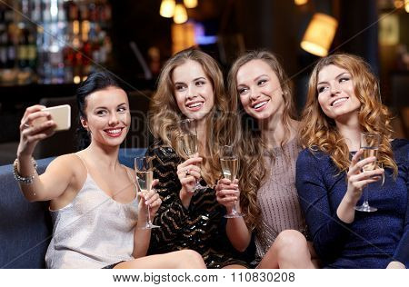 celebration, friends, bachelorette party, technology and holidays concept - happy women with champagne and smartphone taking selfie at night club