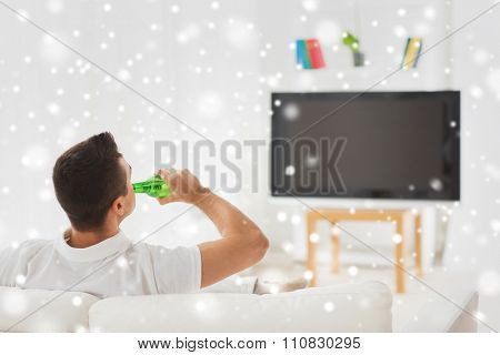 leisure, technology, mass media and people concept - man watching tv and drinking bottle beer at home from back over snow effect