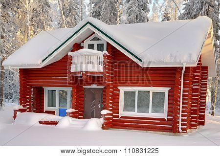 Wooden Cabin Of Falu Red Dyed Timber, With Snow-covered Roof.