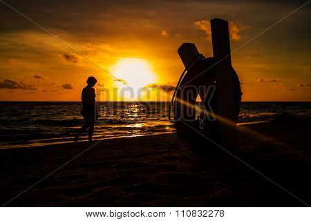Beautiful sunset with silhouette of woman walking on a beach