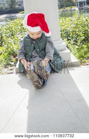 Melancholy Mixed Race Boy Sitting At The Park Wearing Christmas Santa Hat.