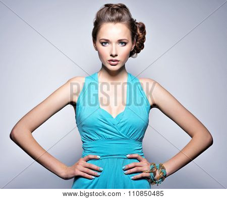 Young beautiful woman with jewelry. Girl Fashion model in blue dress wearing bijouterie.