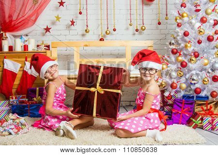 Two Funny Girl Holding A Great Gift Sitting On A Rug