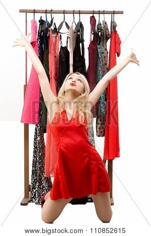 beautiful blond girl in a red dress in front of a clothes hanger. isolated on white background. on h