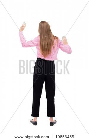 Back view of  business woman.  Raised his fist up in victory sign.    Raised his fist up in victory sign.   Isolated over white background. The girl office worker in black trousers dancing.