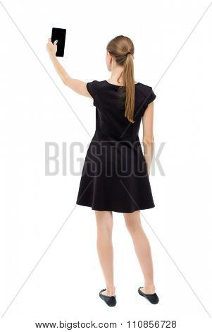 back view of standing young beautiful  girl with tablet computer in the hands of. girl  watching. R  Isolated over white background.The blonde in a black dress makes self on the tablet.