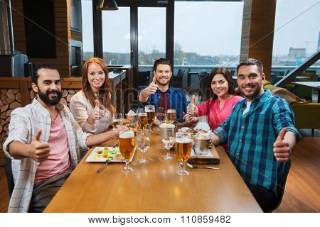 leisure, eating, food and drinks, people and holidays concept - smiling friends having dinner and drinking beer and showing thumbs up at restaurant or pub
