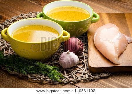 Chicken bouillon in the bowls on the rustic wooden background.