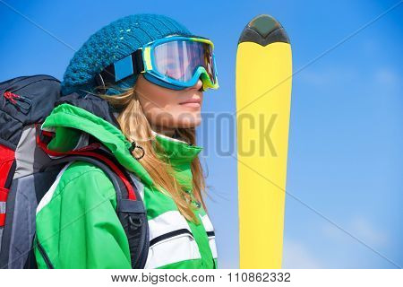 Portrait of cute skier girl wearing sportive mask holding yellow ski over blue background, spending happy active winter holidays in the mountains