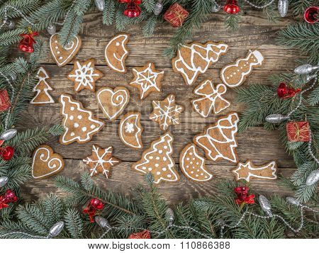 Christmas framework arranged from spruce branches placed on wooden rustic boards with seasonal shape gingerbread cookies with white icing