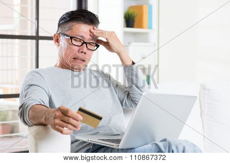 Portrait of 50s mature Asian man having problems while using computer internet doing online payment with credit card, sitting on sofa at home.