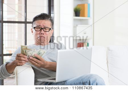 Financial problem concept. Portrait of 50s mature Asian man counting money with worried expression, sitting on sofa at home.