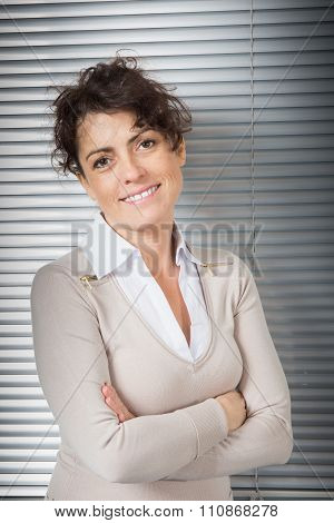Self-assured Woman At Work Standing With Her Hands Crossed  Looking Directly At The Camera