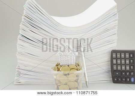 House On A Pile Of Money In Bucket With Pen