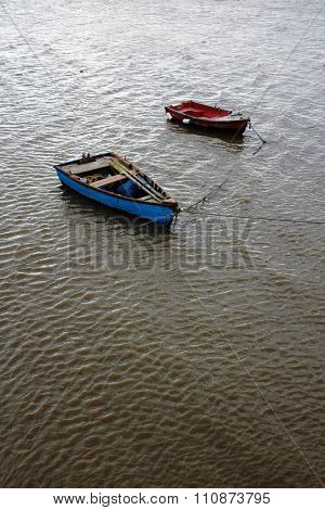 Two row boats anchored in the rippled waters of a river