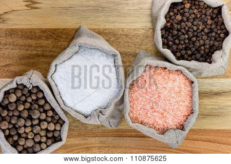 Black pepper, allspice pepper, pink salt, and sea salt in the linen sacks, on the wood