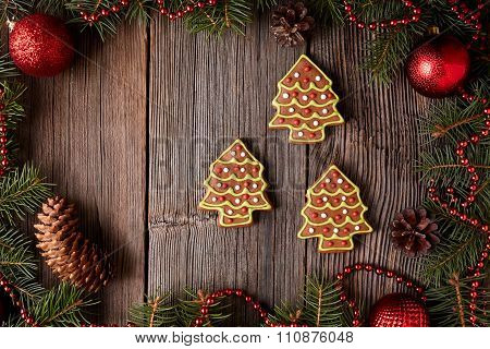 Christmas gingerbread fir trees cookies composition in christmas decorations frame on vintage wooden