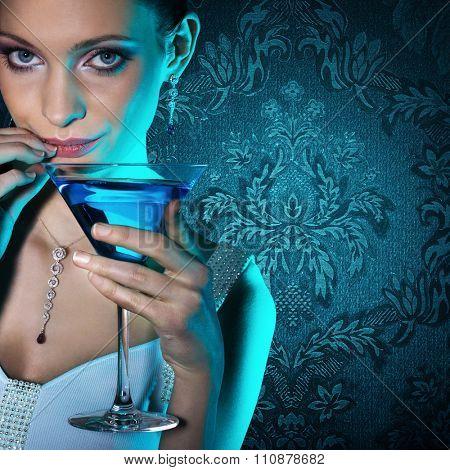 Beautiful woman with martini glass on damask wallpaper background.