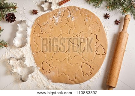 Gingerbread cookies dough preparation recipe with man shape, fir trees, snowman and star forms, cinn