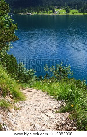 Hiking path along the Achen Lake (Achensee) with high mountain background during summer time