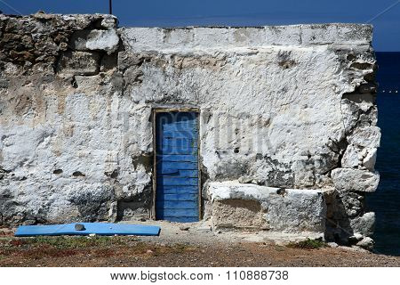 Old whitewashed wall with blue door