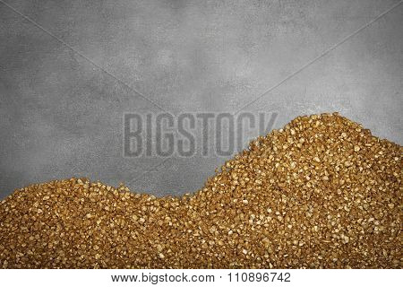 A corner of Gold nugget grains, on cement background