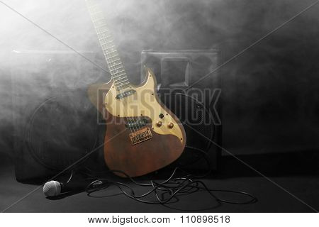 Big loudspeakers with electric guitar and microphone in dense smoke on black background