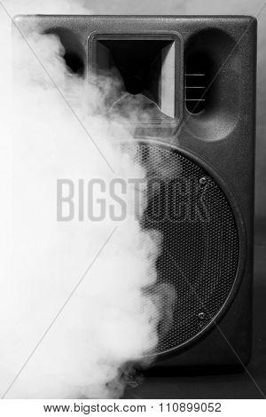 Big loudspeaker in a smoke on black background