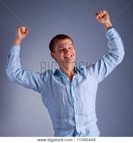 portrait of young happy man with raised hands