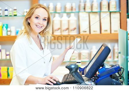 portrait of cheerful smiling female pharmacist working at the cash register in pharmacy drugstore