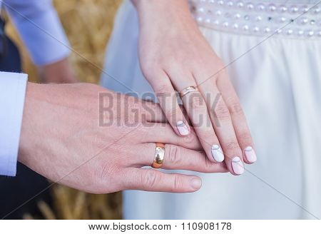 wed couple's hands with wedding rings