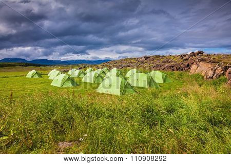 Campground in Iceland. Green tent on a grassy lawn. July in the Arctic