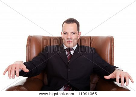 Businessman Upset Seated On A Chair, Isolated On White Background. Studio Shot.