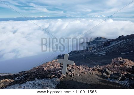 ETNA, SICILY - DECEMBER 05: a lone memorial cross above the white clouds covering Bove Valley in Etna National Park. Shot in 2015