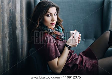 Beautiful young woman with a cup of tea or coffee at  cafe