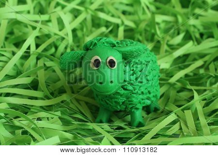 Green  plasticine lamb enclosed with green paper raffia strips